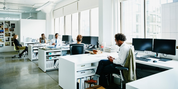 Businesspeople working at workstations in office