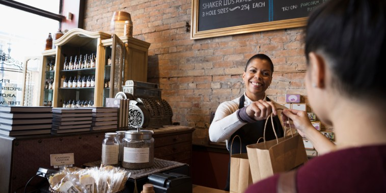 Smiling female spice shop owner giving shopping bags to customer at counter