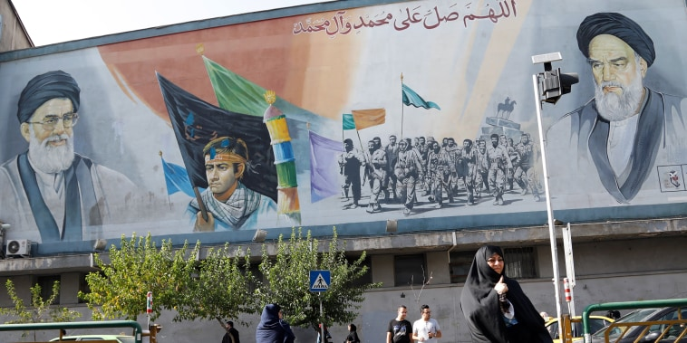 Image: A woman walks under a wall painting in Tehran