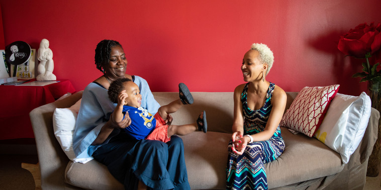 """Mary Jackson, a licensed CLC and Vice President of Reaching Our Sisters Everywhere, Inc. (""""ROSE""""), sits with NickeySue Christian and her son Mark."""