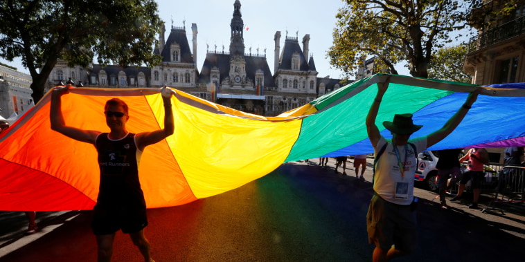 People display a huge rainbow flag as they participate at the international Rainbow Memorial Run during the inauguration of the Gay Games village at the Hotel de Ville city hall in Paris