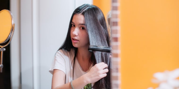 Woman using hair straightener