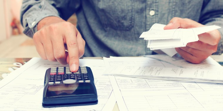 Image: Man With Calculator and Bills at Desk At Office