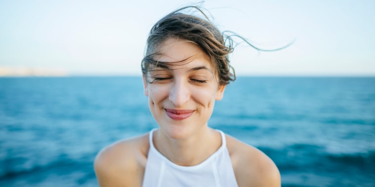Young woman smiling with eyes closed with sea background