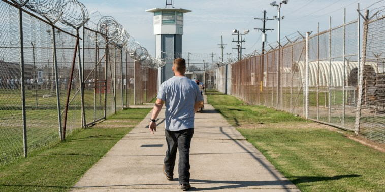 A prisoner walks thru a fenced section toward a guard tower at Angola Prison in 2013.