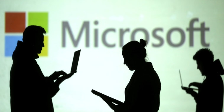 Image: Silhouettes of laptop users are seen next to a screen projection of Microsoft logo in this picture illustration