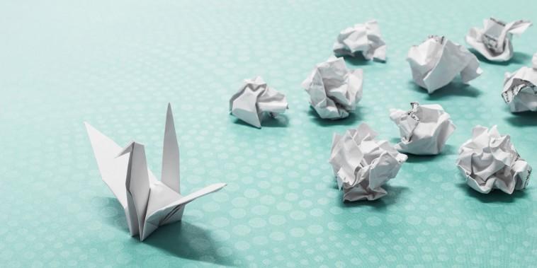 Success concept, A origami paper bird and crumpled paper balls