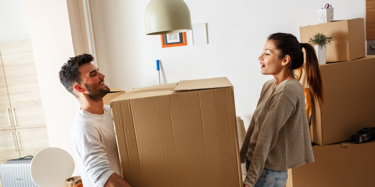 Image: A man and woman carry a box
