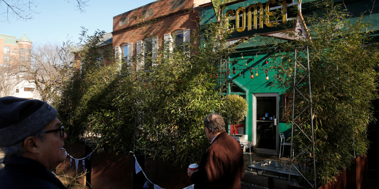 People walk past the Comet Ping Pong pizza restaurant in Washington