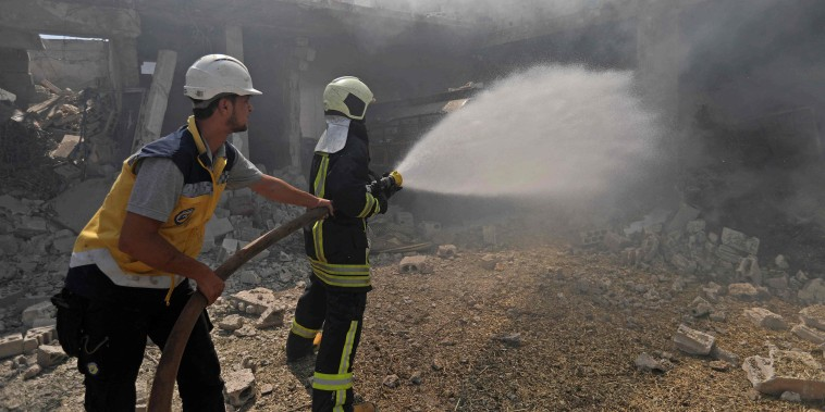 Image: Firefighters battle a blaze after an airstrike in Jadraya, Syria