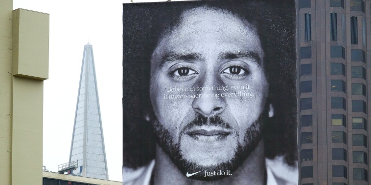 Image: A large billboard stands on top of a Nike store showing former San Francisco 49ers quarterback Colin Kaepernick