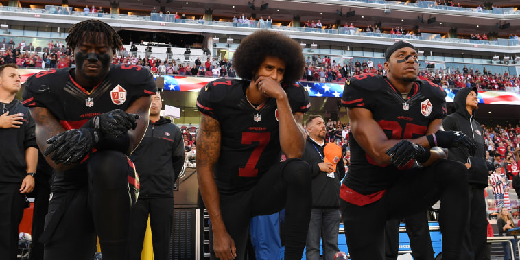 Image: Eli Harold, from left, Colin Kaepernick, and Eric Reid of the San Francisco 49ers kneel in protest during the national anthem
