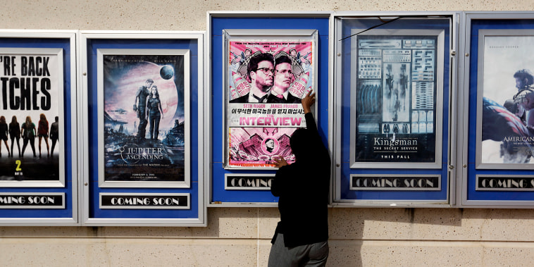 """A poster for the movie """"The Interview"""" is taken down by a worker after being pulled from a display case at a Carmike Cinemas movie theater on Dec. 17, 2014, in Atlanta. The cinema decided to cancel its planned showings of """"The Interview"""" in the wake of threats against theatergoers by the Sony hackers."""