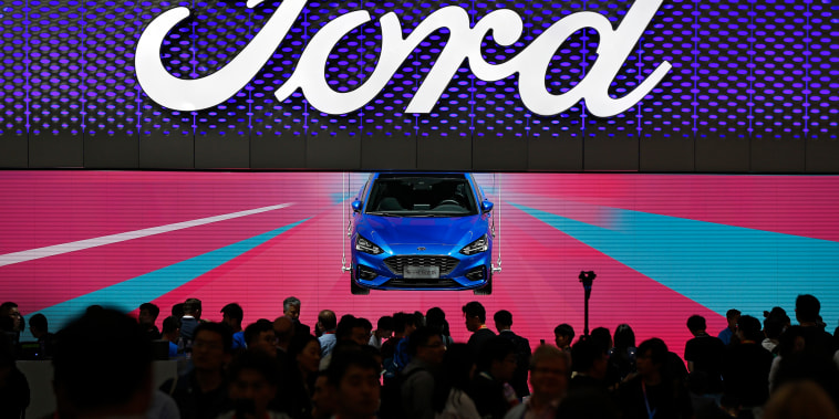 Visitors and journalists crowd near a Ford Focus on display at the Ford exhibit during the media day for the China Auto Show in Beijing on April 25, 2018.
