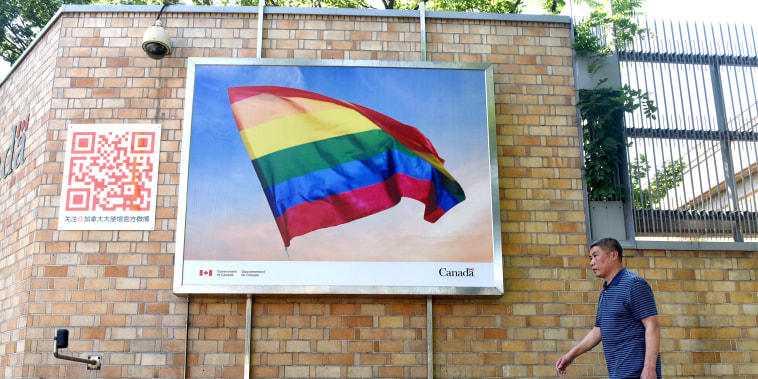 A man walks past a poster of a rainbow flag outside the Canadian embassy in Beijing on May 18, 2018.