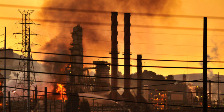Image: Firefighters douse a flame at a Chevron oil refinery in Richmond, California