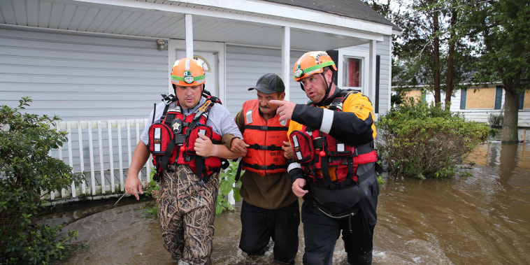 Image: Lumberton North Carolina Fire and Rescue members help a resident walk through flooded waters