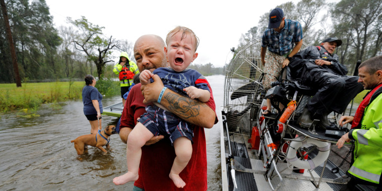 Image: Oliver Kelly, 1 year old, cries as he is carried off the sheriff's airboat during his rescue from rising flood waters in the aftermath of Hurricane Florence in Leland, North Carolina