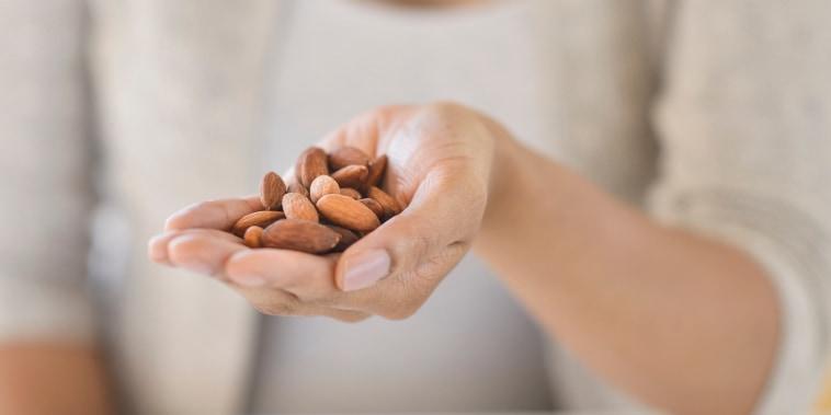 USA, New Jersey, Jersey City, Close-up of woman holding almonds