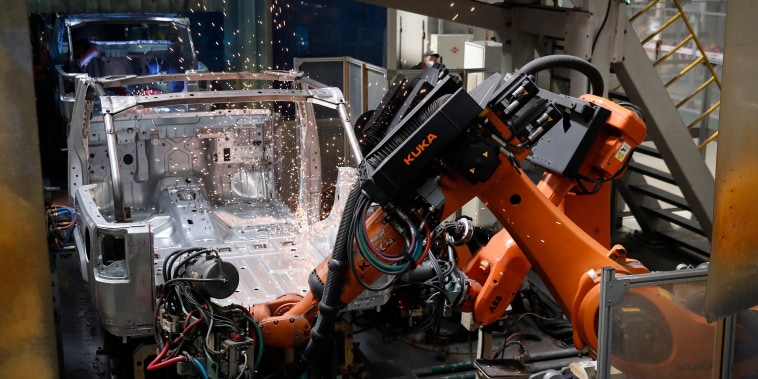 Image: Robotic arms and workers make welds on a BAIC Jeep chassis frame at the Chinese automaker BAIC ORU assembly plant in Beijing