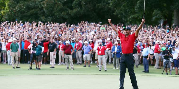 Image: Tiger Woods of the United States celebrates making a par on the 18th green to win the TOUR Championship at East Lake Golf Club