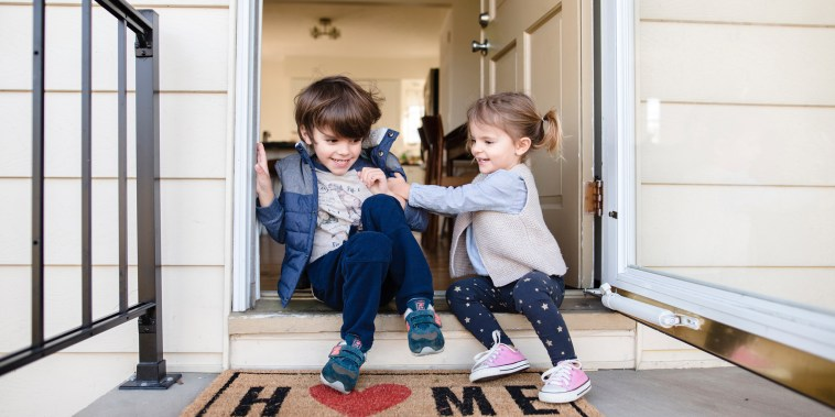 Image: Young boy and girl sitting side by side on the front step of a house, teasing each other and smiling.