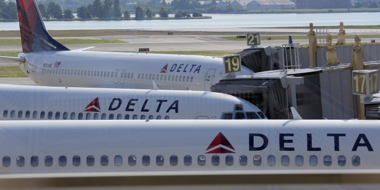 Image: Delta Airlines planes are parked at gates at Ronald Reagan Washington National Airport in Washington