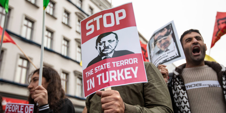 Image: A demonstrator holds a banner depicting Turkish President Erdogan in Berlin