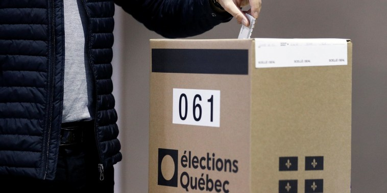 Image: A man votes at a polling station in Quebec City