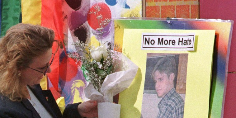 Kate Keating places flowers on the picture of Matthew Shepard during a memorial in Denver Oct. 12, 1998.