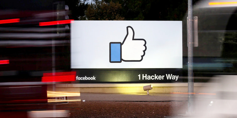 Image: The entrance sign to Facebook headquarters is seen through two moving buses in Menlo Park