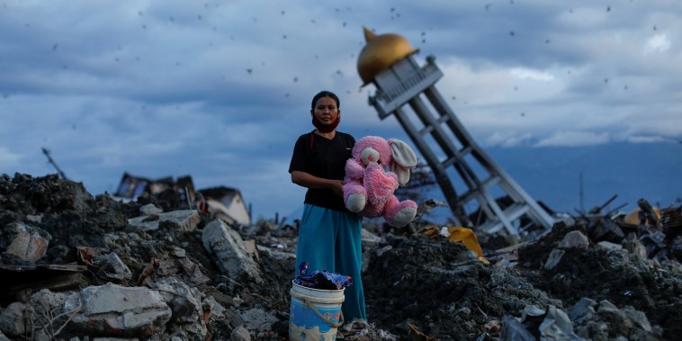 A woman holds a stuffed rabbit toy after it was found at her destroyed home where she said she had lost her three children, in Palu