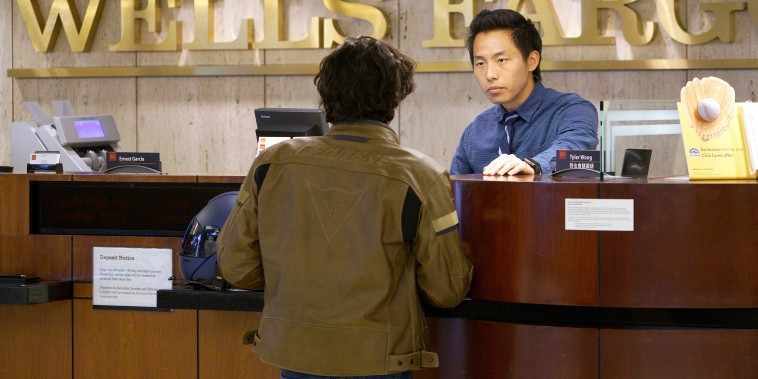 Bank Teller Tyler Wong talks to a customer at the Wells Fargo bank in Denver on April 13, 2016.