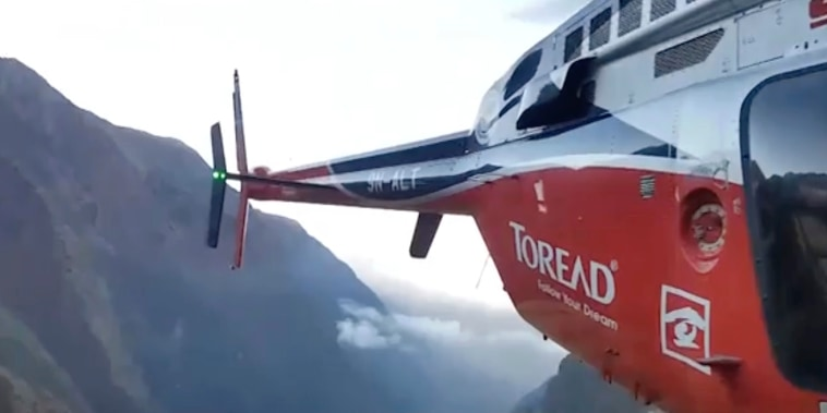 In this grab taken from video provided by SIMRIK AIR, a helicopter lands close to a storm site after searching for missing mountaineers on the Gurja Himal mountain, in Nepal, Saturday, Oct. 13, 2018.