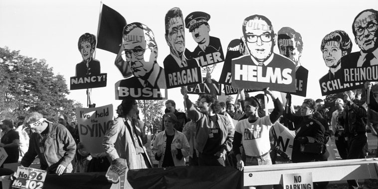 "Members of AIDS activist group ACT UP hold a banner stating ""Silence Equals Death"" and signs of George W. Bush, Ronald Reagan, Nancy Reagan, Jesse Helms and others with ""Guilty"" stamped on their foreheads at Food and Drug Administration headquarters on Oct. 11, 1988, in Rockville, Maryland."