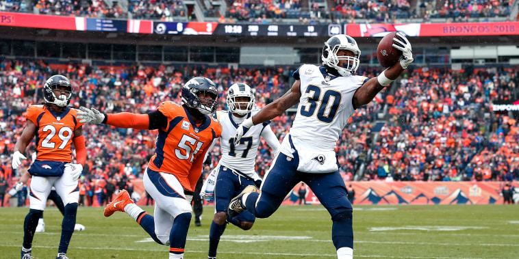 Los Angeles Rams running back Todd Gurley II (30) runs for a touchdown ahead of Denver Broncos linebacker Todd Davis (51) in the second quarter at Broncos Stadium at Mile High in Denver, Colorado on Oct 14, 2018.