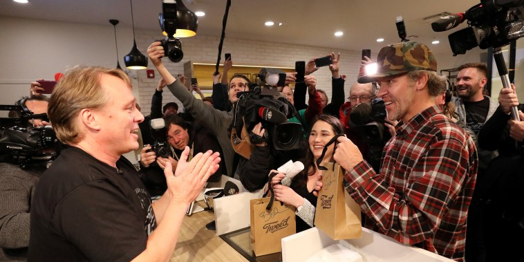 Image: Canopy Growth CEO Bruce Linton applauds after handing Ian Power and Nikki Rose, who were first in line to purchase the first legal recreational marijuana after midnight, their purchases at a Tweed retail store in St John's