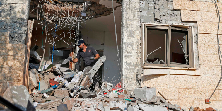 Image: An Israeli sapper checks a house after it was hit by a rocket fired from the Hamas-run Palestinian Gaza Strip,