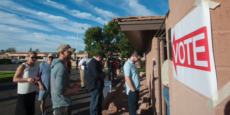 Image: Voters wait in line in front of a polling station  in Scottsdale, Arizona