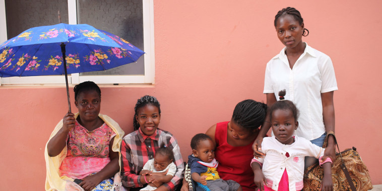 Mothers wait with their children outside the Neurosurgical and Hydrocephalus Treatment Center in Luanda
