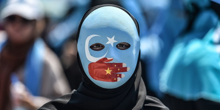 Image: A demonstrator in Istanbul denounces China's treatment of ethnic Uighur Muslims.