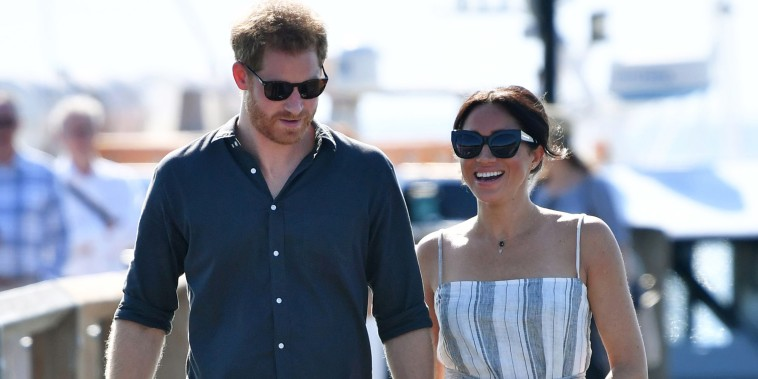 Meghan Markle wears a casual dress and cradles her baby bump in Australia.