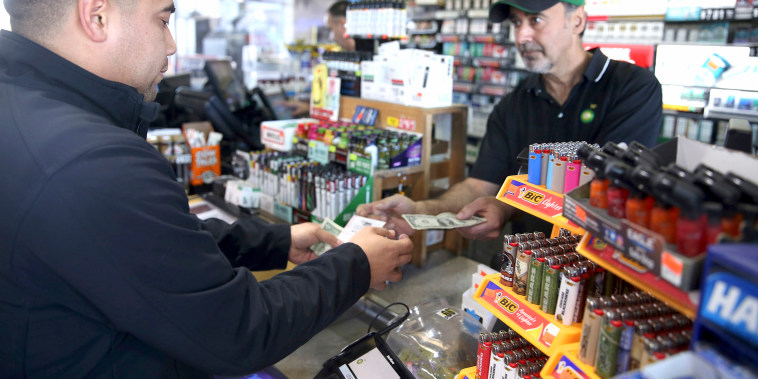 Image: Clerk Zoheir Jendo, right, sells lottery tickets to Jose Reyna of Hampshire at the Stark's Corner Market BP gas station in Pingree Grove, Illinois on Oct. 22, 2018.
