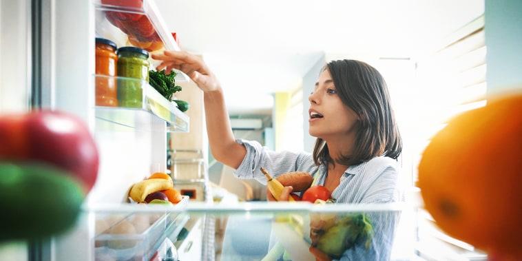 A woman reaches into a refrigerator