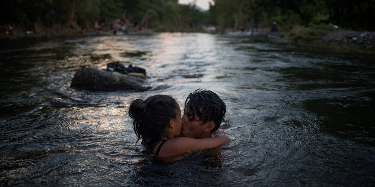 Image: Couple kiss in Rio Novillero as caravan from Central America en route to U.S. stops in San Pedro Tapanatepec, Mexico