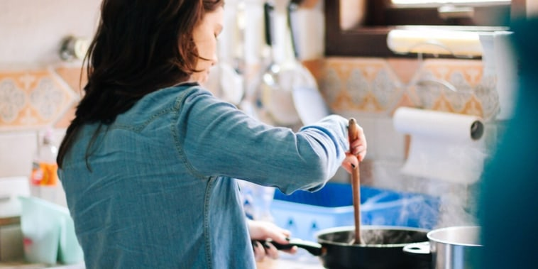 Side View Of Woman Cooking Food In Kitchen At Home