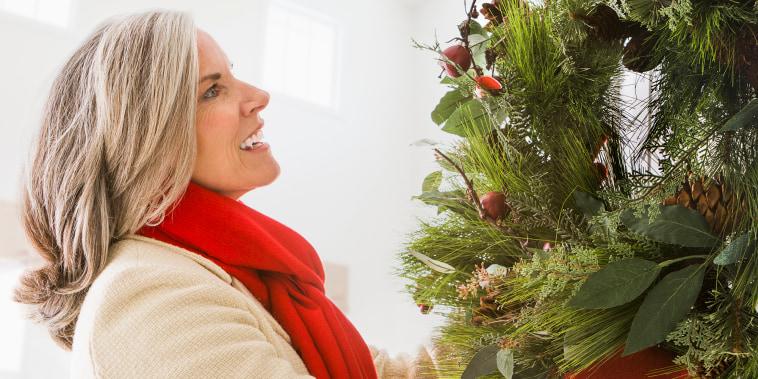 Caucasian woman hanging Christmas wreath on door