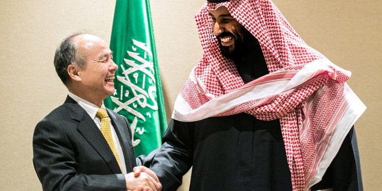 Image: Masayoshi Son, chairman and chief executive officer of SoftBank Group Corp., left, shakes hands with Mohammed bin Salman, Saudi Arabia's crown prince, after signing an agreement in New York