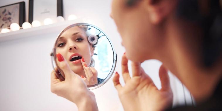 Image: Mirror image of woman applying lipstick