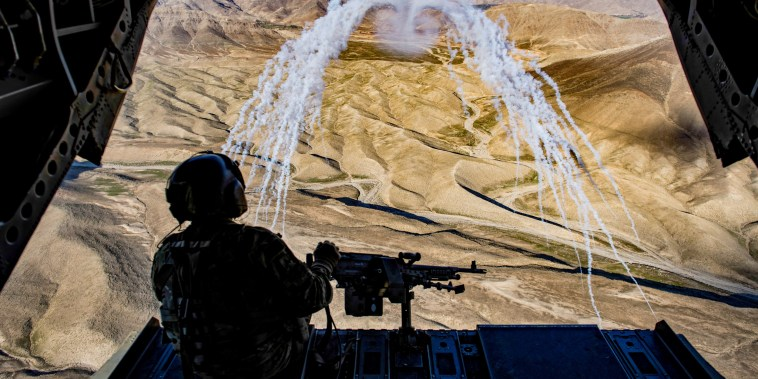 Image: A U.S. Army crew chief flying on board a Chinook helicopter observes the successful test of flares during a training flight in Afghanistan